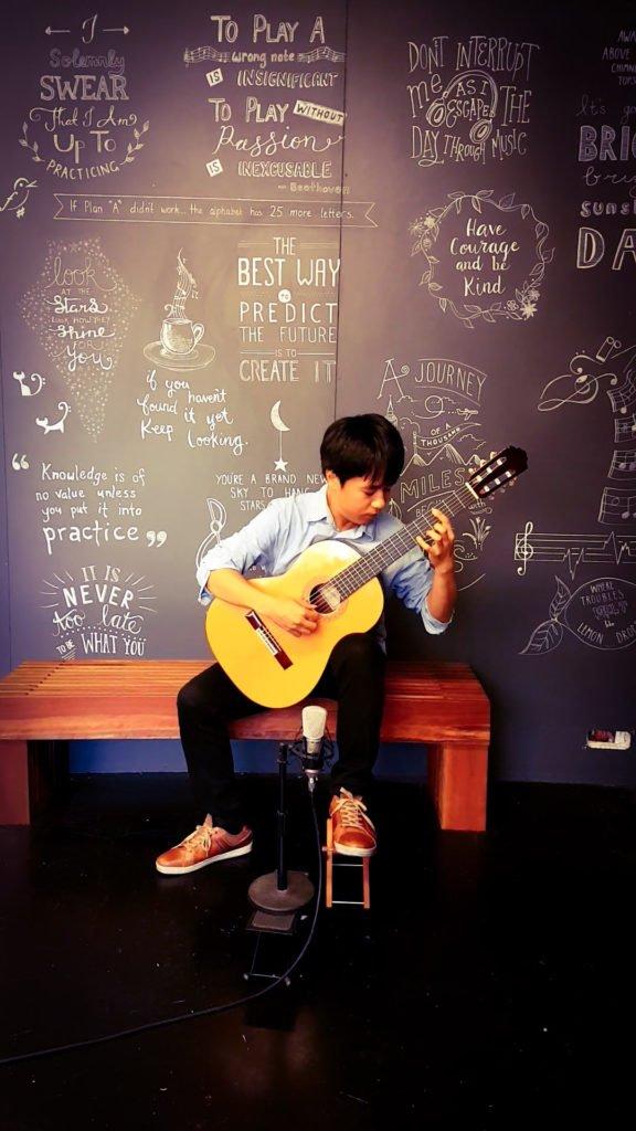 Yuki Osa performing at Stratford Music with his Acoustic Guitar.